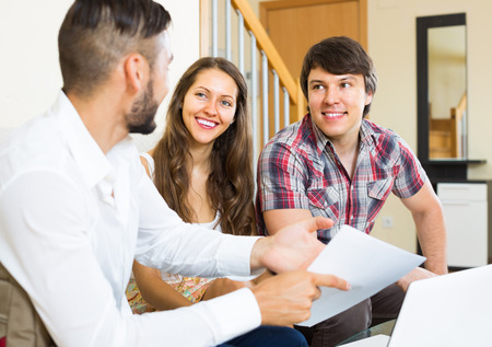 salesman: Smiling salesman talking with young man and woman about purchase at their home Stock Photo
