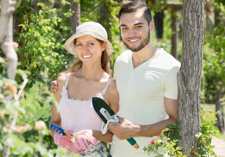 floriculturist: Cheerful married couple in flowers garden smiling at summer day Stock Photo