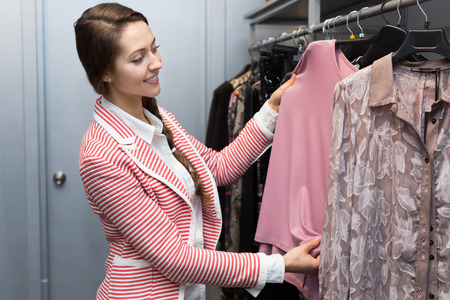 renewing: Apparel shop: attractive female renewing her wardrobe Stock Photo