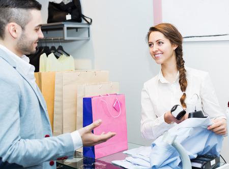 store clerk: Store clerk serving purchaser at cash register desk Stock Photo