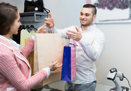 cash register: Positive smiling client paying for new apparel at store counter