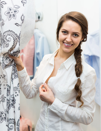 brune: Positive young woman standing at boutique changing cubicle