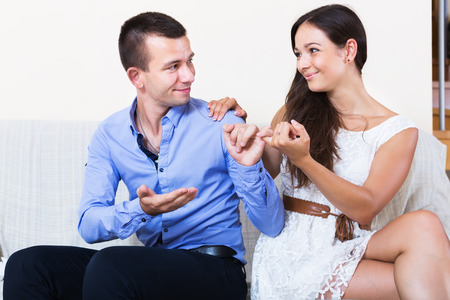spouse: Relaxed spouse forgiving partner for words and actions at sofa. Focus on man