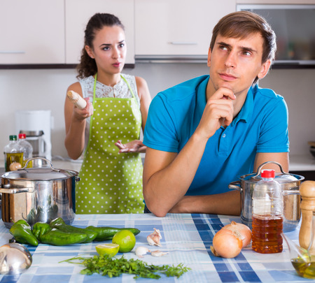 spouse: Unpleased woman criticizing young spouse in domestic kitchen Stock Photo