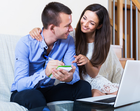 spouses: Young spouses sitting in front of laptop and making notes. Focus on woman