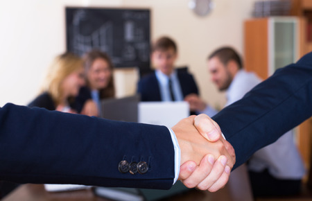 deal in: Managers shaking hands after successful deal in office Stock Photo