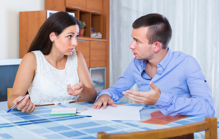 money problems: Family couple with money problems making shopping list indoors Stock Photo