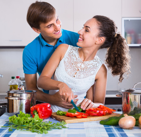 25s: Happy young couple near table with vegetables at home kitchen Stock Photo
