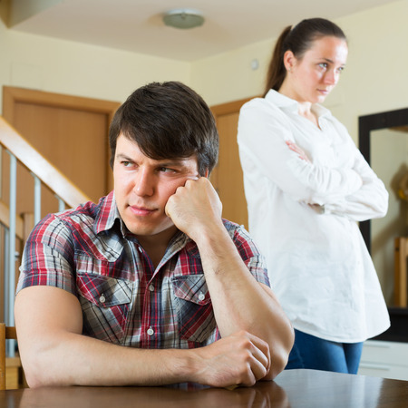 squabble: Sad guy and unhappy woman during conflict in living room at home Stock Photo