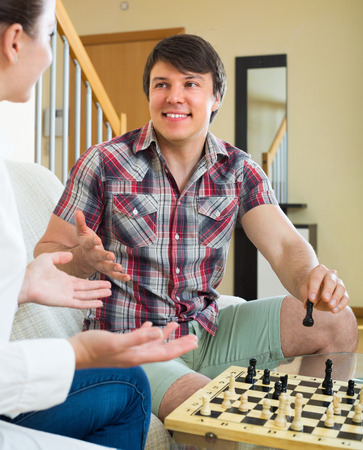 cosy: Man and woman playing chess sitting in a cosy room Stock Photo
