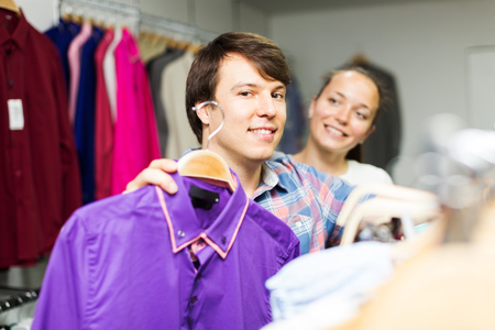 choosing clothes: Positive couple choosing clothes in the shop