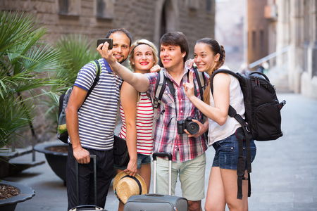 student travel: Young smiling travelers walking through the city and doing selfie