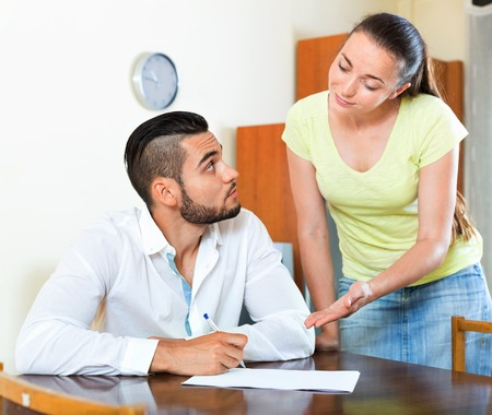 strife: Worried serious male and female sitting with business papers