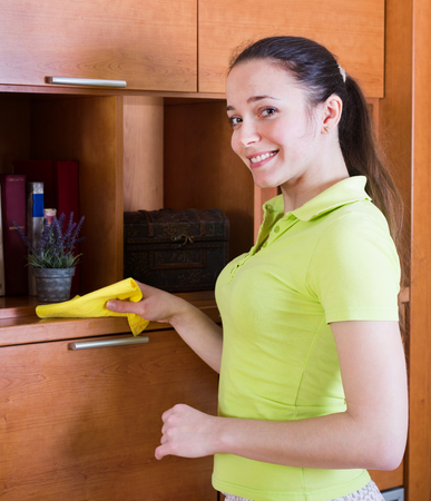wiping: Woman in green wiping the dust from wooden furniture at home