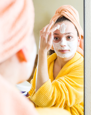 freetime: Reflection of a woman in a mirror in bathroom taking care of skin on her face Stock Photo
