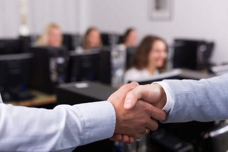 customer: Satisfied adult customer service manager shaking hand of employee
