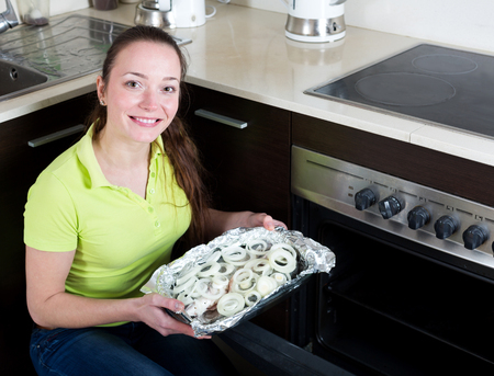 gilthead bream: Smiling woman cooking fish  in oven at home kitchen