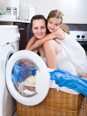 laundry room: smiling russian  housewife and her daughter with linen near washing machine