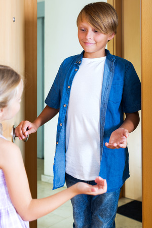 expected: Cheerful kid welcoming friend in doorway and smiling Stock Photo