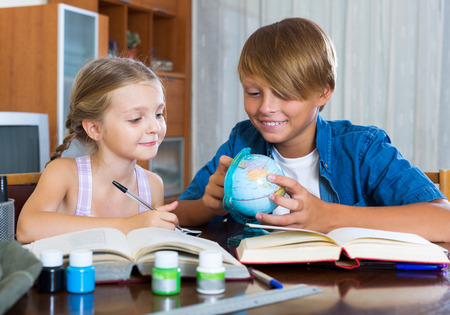 big brother: Big brother helping little girl to do homework at home Stock Photo