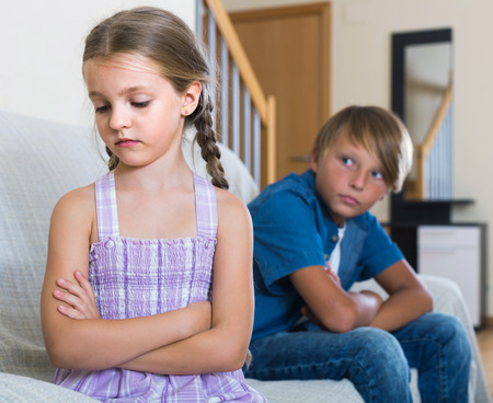 berate: Teenage russian boy and sad little girl quarrelling at home. focus on girl