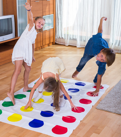 twister: Group of happy children playing at twister inside