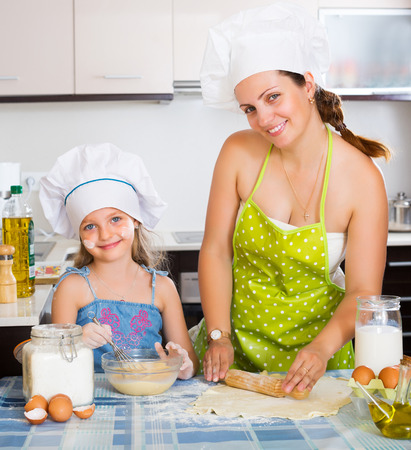 sheeting: Happy young mom and little daughter sheeting dough and smiling Stock Photo