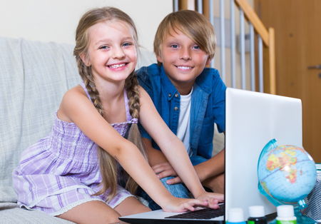 girl friends: Portrait of happy smiling children busy with game on laptop