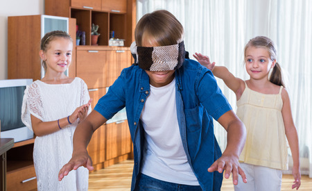 blind man: happy russian children playing at Blind man bluff indoors Stock Photo