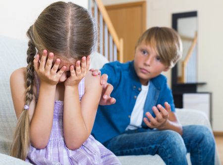 berate: Teenage boy and unhappy american little girl quarrelling at home. focus on girl