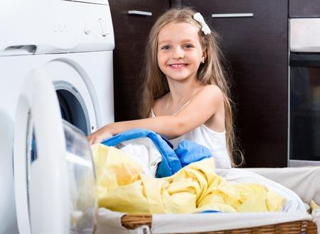 lavando ropa: Sonriente niña disfrutando del olor de la ropa lavada