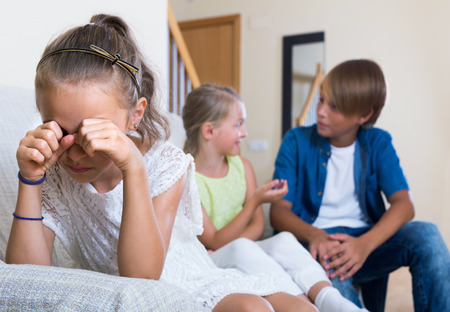 amorousness: First amorousness: unhappy european girl and couple of kids apart indoors