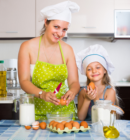 30s adult: Portrait of happy mother in apron and child making omelette at kitchen