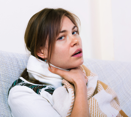 sickly: Young unhappy woman having heavy sickly tonsillitis in domestic interior
