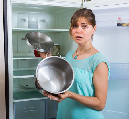 starving: Frustrated starving girl standing near empty fridge