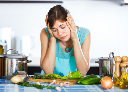 reluctance: Young woman with sad face cooking dinner at home interior Stock Photo