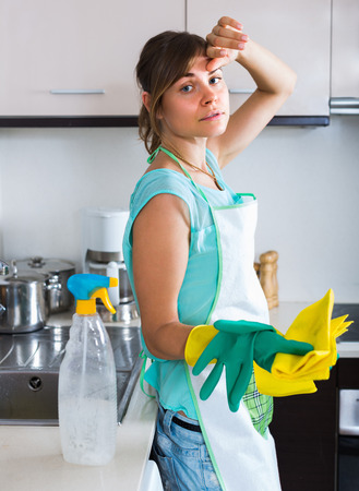 householder: Portrait of young brunette tired to clean indoors