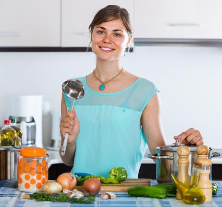 kitchen spanish: Young spanish woman preparing vegetarian soup on residential kitchen