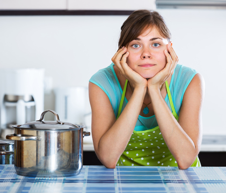 unwillingness: Young woman with sad face cooking dinner at home
