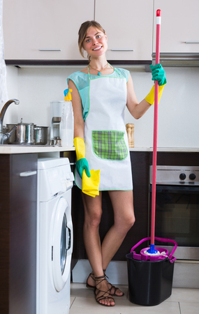 householder: Smiling young woman with mop and bucket in residential kitchen Stock Photo