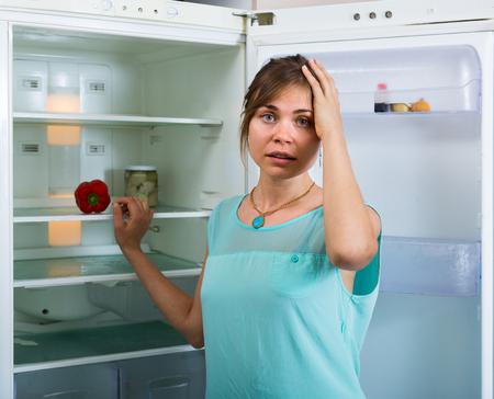refrigerador: Retrato de infeliz y hambre niña cerca de la nevera vacía
