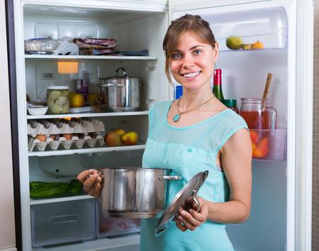 householder: Smiling brunette girl standing near refrigerator full of food