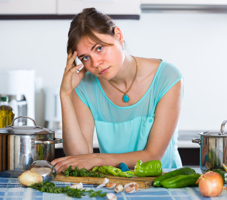 householder: Portrait of exhausted young woman posing at home kitchen Stock Photo