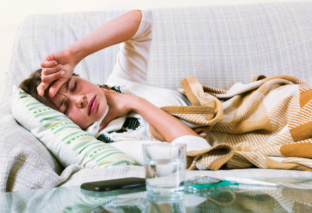 domestic interior: Young woman having heavy quinsy in domestic interior Stock Photo