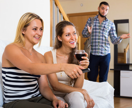 cheater: Surprised guy discovering his young girlfriend with another girl at home Stock Photo