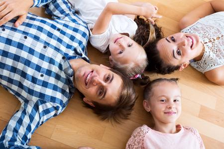 Lächelnd Eltern mit zwei kleinen Töchter zu Hause entspannen