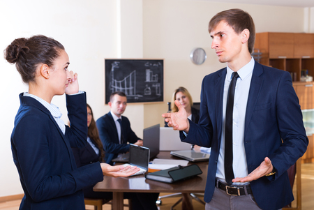 Manager lecturing team member severely at office meeting Stock Photo