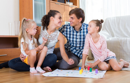 relaxed: Cheerful young parents and two little daughters playing board game at home
