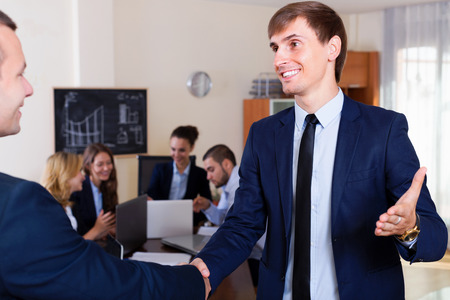employee development: chief greeting a new employee and shaking hands in office