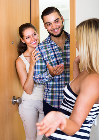 warmly: Cheerful young couple warmly greeting friend at the doorway. Focus on guy Stock Photo